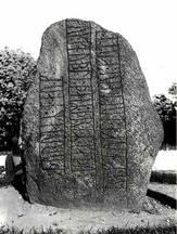 Sort/hvidt foto af runesten med tre rækker tekst. Stammer fra Bække i Jylland. Indskriften lyder  'Ravnunge-Tue og Funden og Gnyble, de tre gjorde Thyres høj'. Foto: Nationalmuseet.