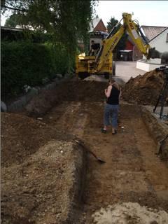 Billedet viser en udgravningsgrøft, hvor gravemaskinen ses i baggrunden.