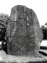 Black and white photo of rune stone with three rows of text from Bække in Jutland. The inscription reads 'Ravnunge-Tue and Funden and Gnyple, those three made Thorvi's mound'. Photo: the National Museum.