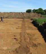 Billedet viser udgravningen af den østlige pallisade i Jelling . Pallisadens forløb ses som en mørkere aftegning i jorden.