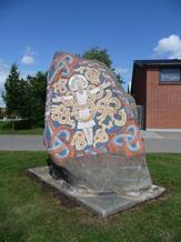 Photo showing the rune stone in Viborg, looking at the side with the Christ figure. The figure is painted with bright colours.