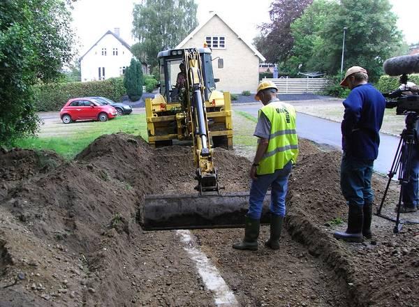 Billedet viser den lille gule gravemaskine, som afdækker et nyere fundament. Dette ses som en lysere streg i jorden.