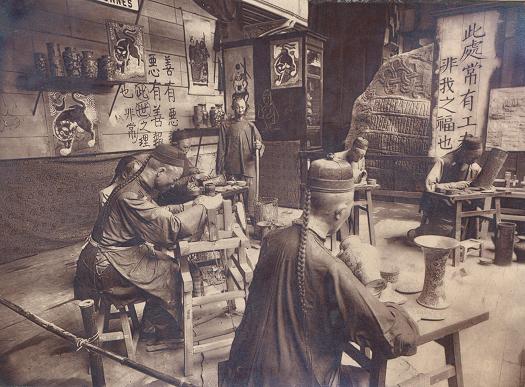Kopi af Harald Blåtands runesten ved indgangen til den danske udstilling i Paris, 1889. I forgrunden kinesiske kunsthåndværkere. Foto: Musée d'Archeologie Nationale, Château de Saint-Germain.